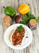 Roasted chicken fillets on white plate and vegetables, on wooden background — Stock Photo