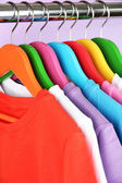 Different shirts on colorful hangers on purple background — Stock Photo