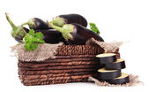 Fresh eggplants in wicker basket isolated on white — Stock Photo