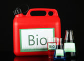Bio fuels in canister and vials on black background — Stock Photo