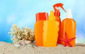 şişe mavi zemin üzerine güneş kremi — Stok fotoğraf