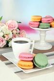 Café y pastas en mesa sobre fondo claro — Foto de Stock