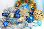Adornos navideños en florero de cristal sobre fondo de tela — Foto de Stock