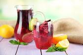 Limonada de albahaca roja en jarra y vidrio, en la tabla de madera, sobre fondo brillante — Foto de Stock