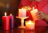 Woman lights candles on bright background — Stock fotografie