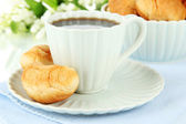 Tasty croissants and cup of coffee on table on white background — Stock Photo