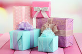 Beautiful bright gifts, on bright wooden table — Stock Photo