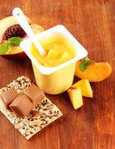 Gustosi yogurt con pezzi di frutta fresca in coppa plastica aperta su fondo in legno — Foto Stock