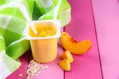 Gustosi yogurt con pezzi di frutta fresca, sul colore di sfondo in legno — Foto Stock