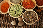 Many different spices and fragrant herbs on braided table close-up — Stockfoto