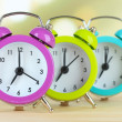 Colorful alarm clocks on table on light background — Stock Photo #32681897