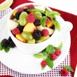 Fruit salad in cup on napkin isolated on white — Стоковая фотография