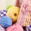 Multicolored clews in wicker basket with plaid closeup — Stock Photo #32682755