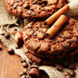 Stock Photo: Homemade cookies with sesame seeds, chocolate, on wooden table, on sackcloth background