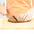 Woman slicing bread with sesame seeds on chopping board, close up — Stock Photo