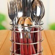 Knives, forks and spoons in metal stand on table on bright background — Stock Photo