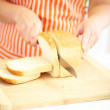 Woman slicing bread on chopping board, close up — Stock Photo #32683413