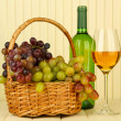 图库照片: Ripe grapes in wicker basket, bottle and glass of wine, on light background