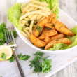 Stock Photo: French fries and home potatoes on plate on board on wooden table