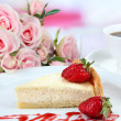 Slice of cheesecake with strawberry on plate, on bright background — Stock Photo
