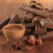 Delicious chocolate bars with cocoa and nuts on wooden background — Stock Photo
