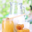 Honey and milk on wooden table on natural background — Stock Photo #32685637