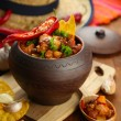 Stock Photo: Chili Corn Carne - traditional mexicfood, in pot, on napkin, on wooden background