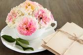 木製の背景にナプキンの上にカップのバラ — ストック写真