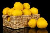 Ripe lemons in wicker basket isolated on black — Stock Photo