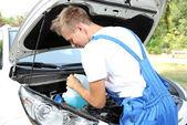 Мужчина наливает жидкость для мытья стекла для автомобилей — Стоковое фото