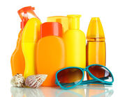 Bottles with suntan cream and sunglasses isolated on white — Stock Photo