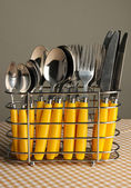 Knives, forks and spoons in metal stand on tablecloth on grey background — Stock Photo