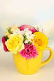 Beautiful bouquet of bright flowers in color mug, on wooden table, on light background — Stock Photo