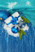 Composition with Christmas balls, gift box and snow on color wooden background — Stock Photo