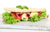 Tasty sandwiches with salami sausage and vegetables on cutting board, isolated on white — Stock Photo