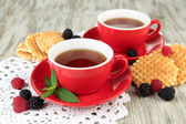 Cups of tea with cookies and berries on table close-up — Stock Photo