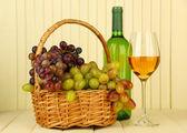 Zralé hrozny v proutěný koš, láhve a sklenky vína, na světlé pozadí — Stock fotografie