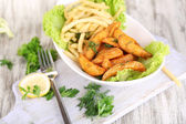 French fries and home potatoes on plate on board on wooden table — Stock Photo