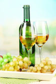Ripe grapes, bottle and glasses of wine on tray, on bright background — Stock Photo