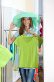 Beautiful girl trying clothes near mirror on room background — Стоковое фото