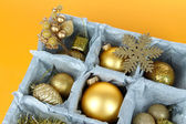 Christmas toys in wooden box on yellow background — Stock Photo