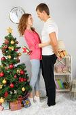 Happy young couple near Christmas tree at home — Zdjęcie stockowe