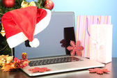 Laptop with gifts on table on blue background — Stok fotoğraf