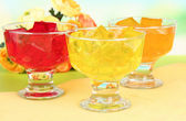 Tasty jelly cubes in bowls on table on light background — Stock Photo