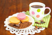 Cocoa in cup with sweets and cocoa powder on plate on wooden table — Stock Photo