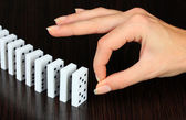 Hand pushing dominoes on wooden background — Stock Photo