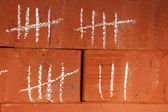 Counting days by drawing sticks on bricks close up — Stock Photo