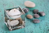Decorative vase with candle, water and stones on wooden table close-up — Stock Photo