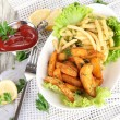 French fries and home potatoes on plate on board on napkin on wooden table — Stock Photo #32775573