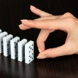Hand pushing dominoes on wooden background — Stock Photo #32776631